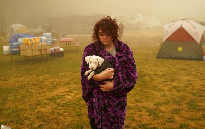 Shayanne Summers holds her dog Toph while wrapped in a blanket after several days of staying in a tent at an evacuation center at the Milwaukie-Portland Elks Lodge.