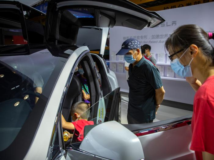 Visitors wearing face masks to protect against the coronavirus look at a Tesla vehicle on display at the China International Fair for Trade in Services (CIFTIS) in Beijing, Saturday, Sept. 5, 2020