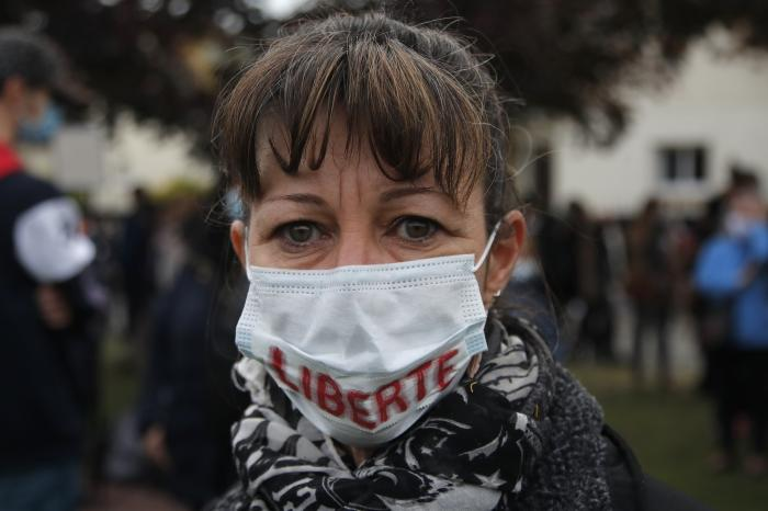 "A woman wears a mask reading ""Freedom"" as residents gather outside the school where a slain history teacher was working, Saturday, Oct. 17, 2020 in Conflans-Sainte-Honorine, northwest of Paris"
