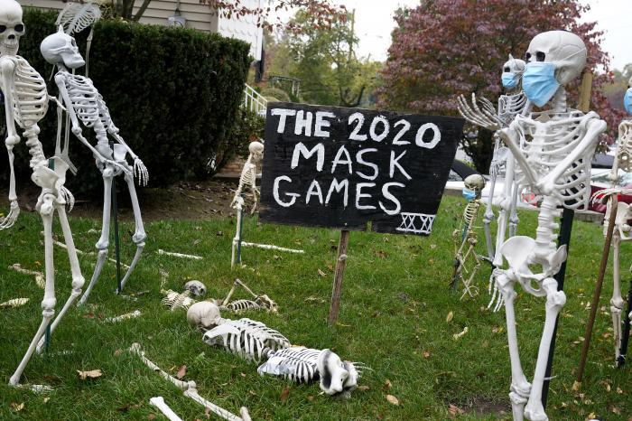 Coronavirus-themed Halloween decorations are displayed on a lawn in Tenafly, N.J.