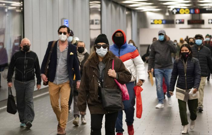 Commuters wear face masks while walking through the World Trade Center's transportation hub in New York.