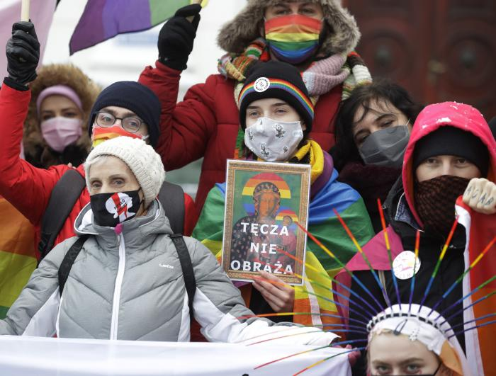 Human rights activists show an altered image with colors symbolizing LGBT rights as they gathered outside the provincial court in Plock, Poland.