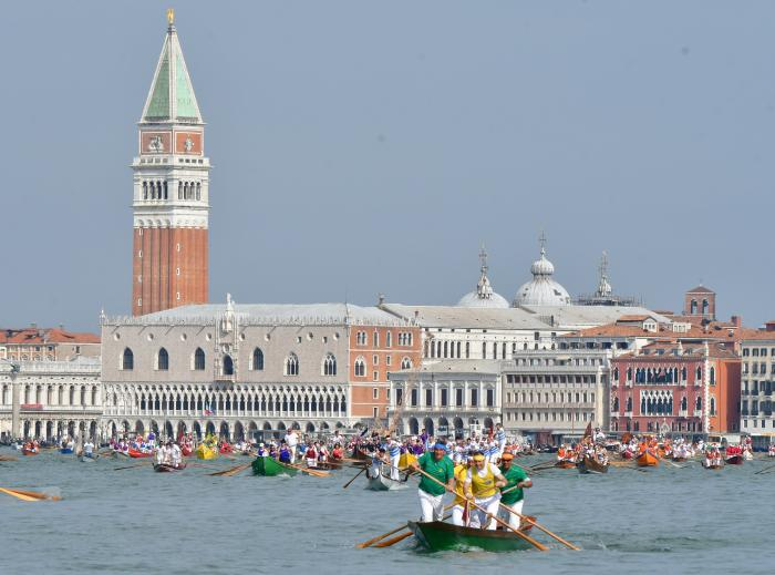 Crews are backdropped by the bell tower of St. Mark's, as they take part in the Vogalonga, a traditional non-competitive rowing boats event, in Venice, Italy, Sunday, May 23, 2021.