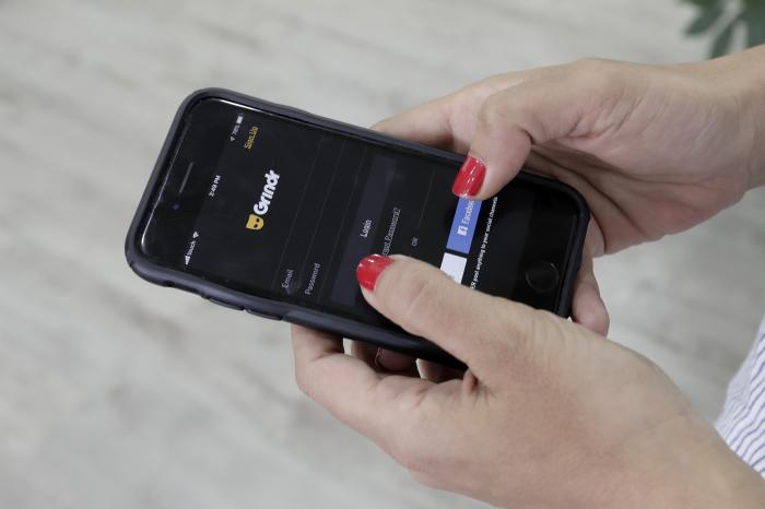 A woman looks at the Grindr app on her mobile phone in Beirut, Lebanon.