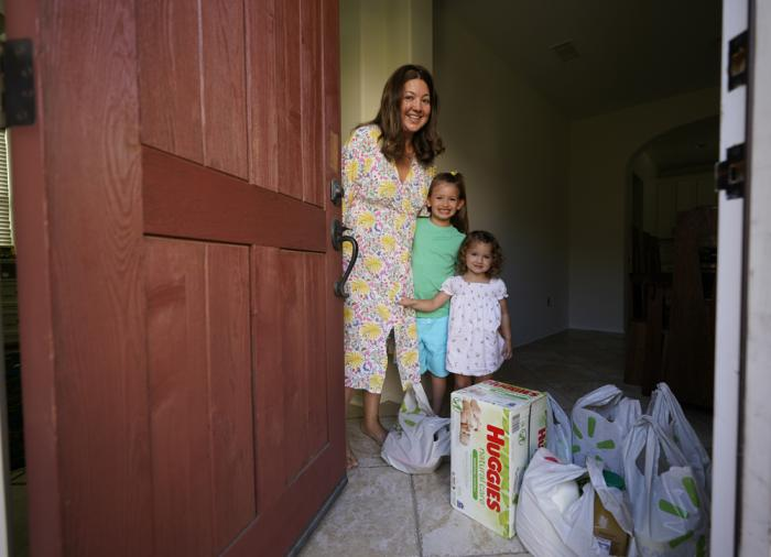 In this July 21, 2021, photo, Cynthia Carrasco White and her daughters, Charlotte, 6 and Mathilde, 3 receive a Walmart purchase delivered by Instacart at their front door home in the Porter Ranch area of Los Angeles