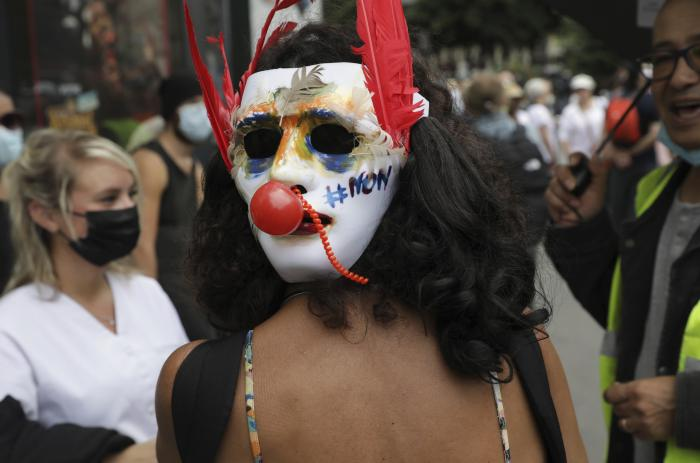 """A protestor wears a mask on the back of her head which says """"no"""" in French as she attends a demonstration in Paris, France, Saturday, July 31, 2021"""