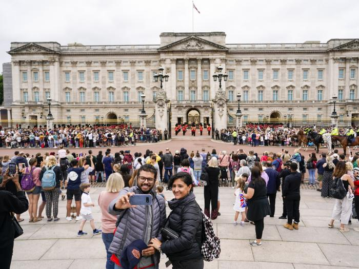 Members of the public watch the Changing of the Guard ceremony at Buckingham Palace, London, Monday August 23, 2021, which is taking place for the first time since the start of the coronavirus pandemic